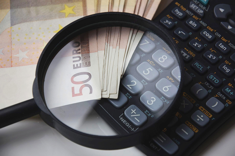 Magnifying glass over calculator. Calculate plusvalía in Torrevieja. Calculate surplus value tax in Torrevieja.