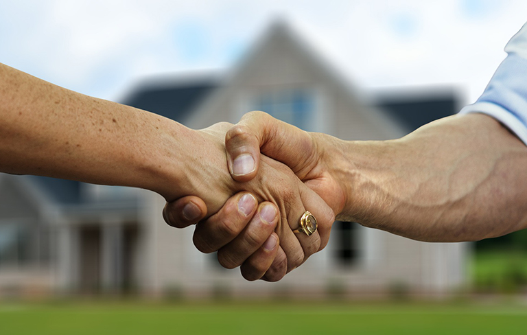 Handshake in front of house. Calculate plusvalía in Torrevieja. Calculate surplus value tax in Torrevieja.