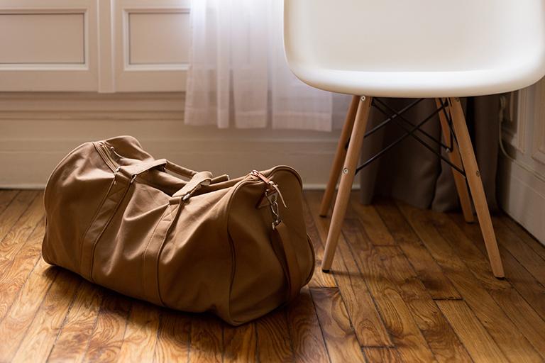Haz las maletas para tu mudanza en Torrevieja. Maleta junto a silla.