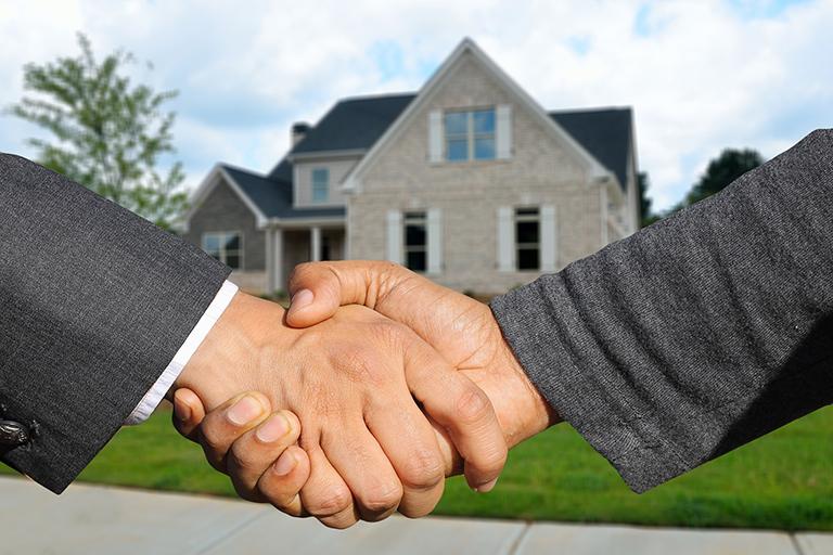Dos hombres dándose la mano frente a una casa vendida.