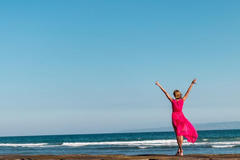Mujer con vestido rosa en la playa. Como limpiar la playa